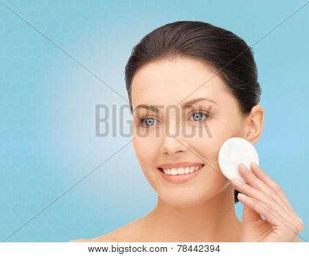 beauty, people and health concept - beautiful smiling woman cleaning face skin with cotton pad over blue background