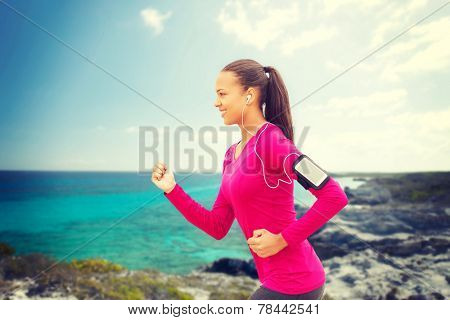 sport, fitness, health, technology and people concept - smiling young african american woman running with smartphone and earphones outdoors