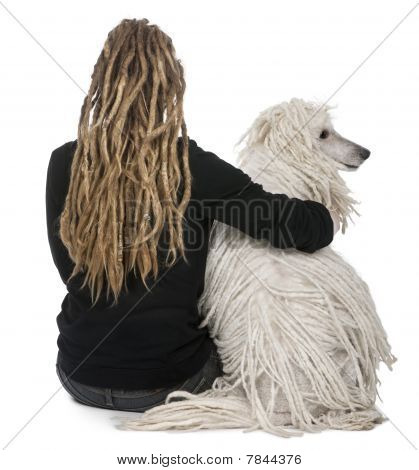 Rear View Of A White Corded Standard Poodle And A Girl With Dreadlocks Sitting In Front Of White Bac