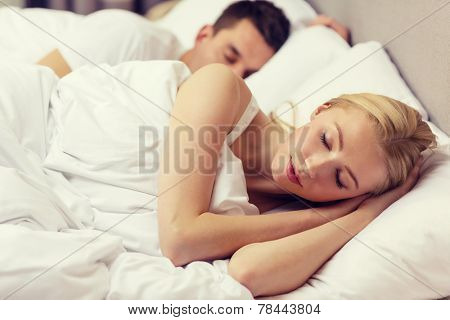 hotel, travel, relationships, and happiness concept - happy couple sleeping in bed