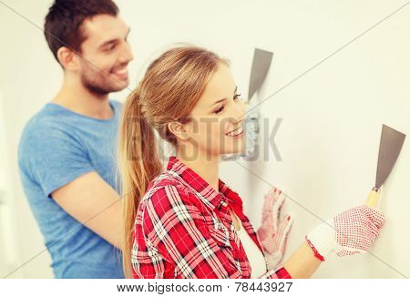 repair, renovation and home concept - smiling couple doing renovations at home