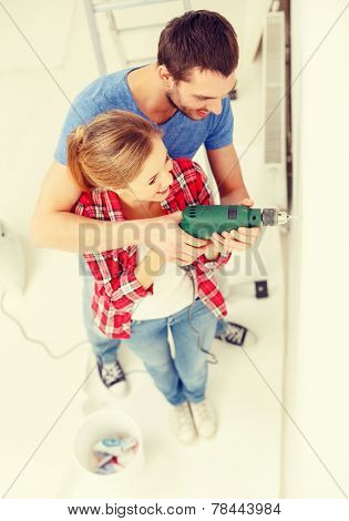 repair, interior design, building, renovation and home concept - smiling couple drilling hole in wall at home