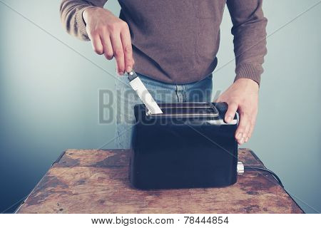 Young Man Sticking Knife In Toaster