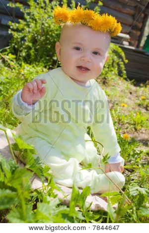 The baby of 7-8 months sits on a grass with a wreath from dandelions on a head and waves discontente