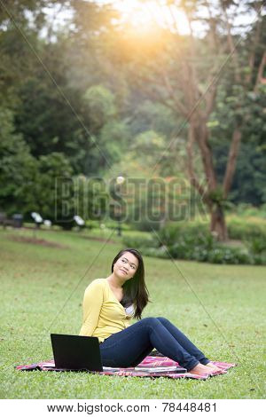 Beautiful young female university or college student thoughtful, with books and laptop, sitting in a park.