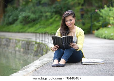 Beautiful young female university or college student reading a book, seated by a lake in a park.