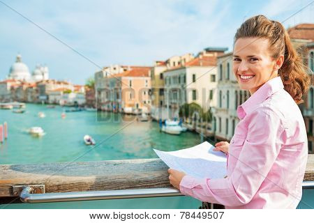 Portrait Of Happy Young Woman With Map Standing On Bridge With Grand Canal View In Venice, Italy