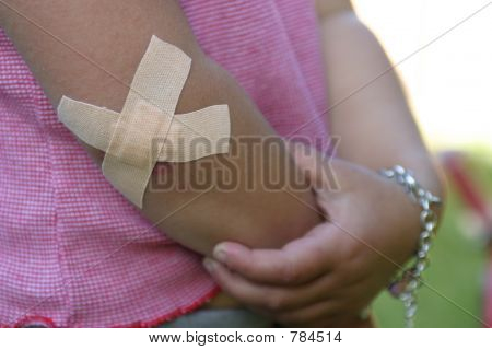 Bandaged elbow, cross of plasters on young girl's arm