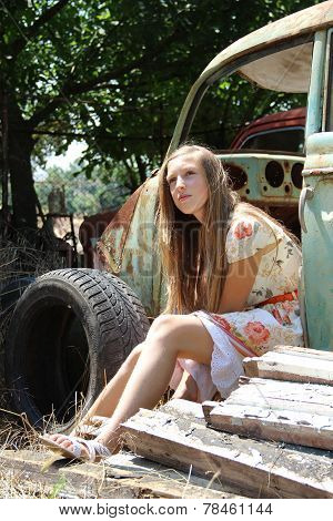 pensive country girl from the old broken car