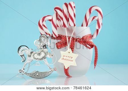 Merry Christmas Silver Vintage Rocking Horse Tree Ornament And Jar Of Red And White Candy Canes On P