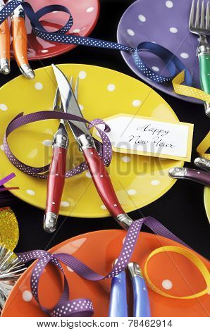 Bright And Colorful Happy New Year Party Dinner Table With Red, Yellow, Orange, Blue, Green, And Pur