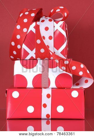 Stack Of Bright Modern Red And White Polka Dot And Check Gift Boxes On A Red Background.