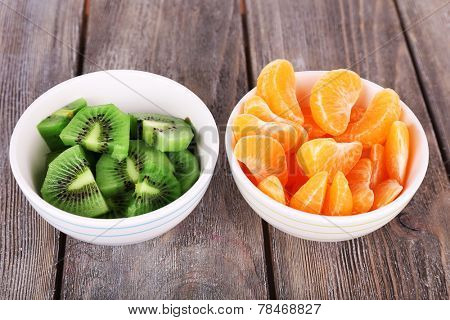 Bowls of slices kiwi and mandarin on rustic wooden background