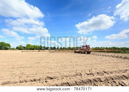 Tractor Working On  Acultivated Field In A Countryside Landscape