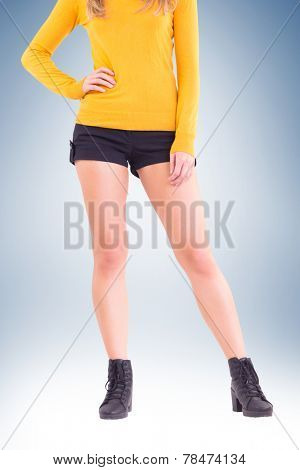 Lower half of woman in boots and shorts on vignette background