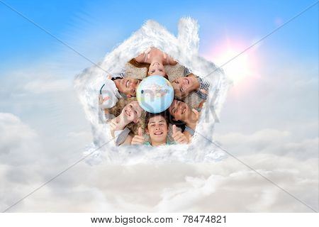 Teenagers on the floor with a terrestrial globe in the center and with thumbs up against blue sky with white clouds