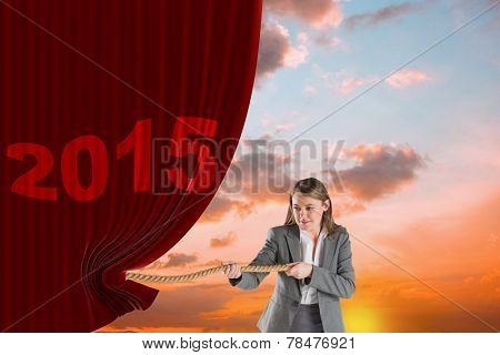 Businesswoman pulling a rope against orange and blue sky with clouds