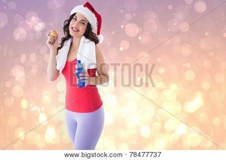 Festive fit brunette holding bottle and apple against pink abstract light spot design