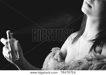 Woman applying perfume on her body B&W
