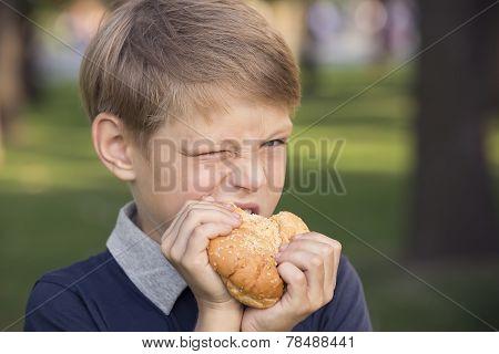 boy outdoors eating a hamburger