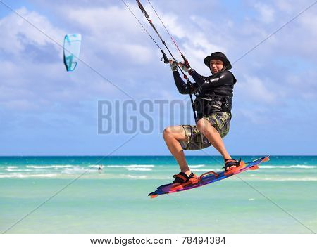 Man in a flight over water. Kitesurfing on the coast of Cuba.