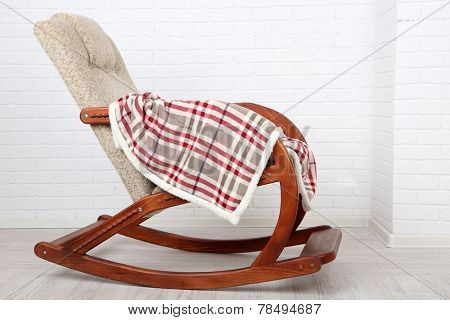 Comfortable rocking-chair with rug on wooden floor near the brick wall background
