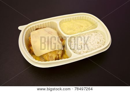 Package for freezing food or to go of parmesan chicken fillet, rice and mashed potatoes on brown background.