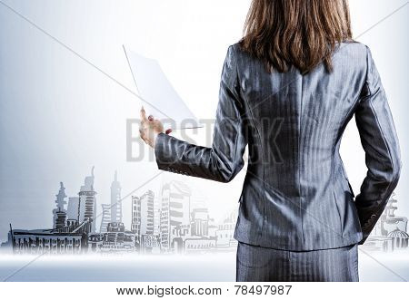 Rear view of businesswoman with papers in hand