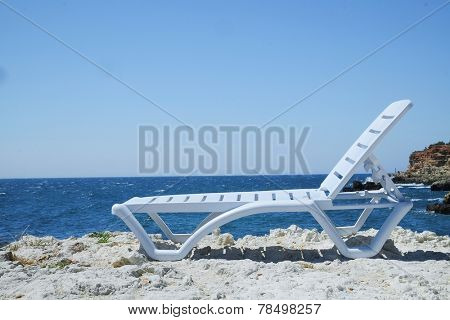 the image of a chaise longue at a sea beach
