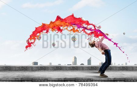 Young guy in casual evading from colorful splashes