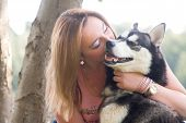 picture of husky  - Young woman and her husky in the forest - JPG