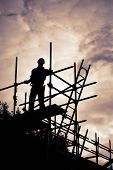 picture of scaffold  - silhouette of construction worker with ladder on scaffolding - JPG