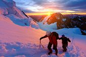 image of mountain-high  - climbers at the top of a pass with backpacks meeting the sunrise in the mountains - JPG