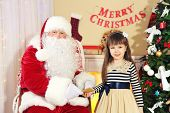 image of letters to santa claus  - Little cute girl giving letter with wishes to Santa Claus near Christmas tree at home - JPG