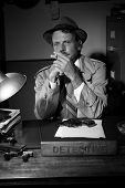 stock photo of trench coat  - Confident detective smoking at desk in trench coat 1950s film noir style - JPG