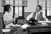 pic of 1950s style  - Director and secretary working together at desk 1950s style office - JPG