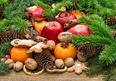 picture of walnut-tree  - Apples mandarin fruits walnuts cookies and spices with christmas tree branches - JPG