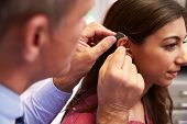 foto of hearing  - Doctor Fitting Female Patient With Hearing Aid - JPG