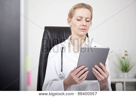 Woman Clinician Looking At Tablet Screen Seriously