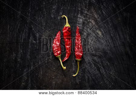 Some Hot Red Peppers Lie On A Dark Board