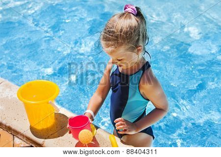 Child with bucket in swimming pool.  Summer outdoor. Playing on beach.