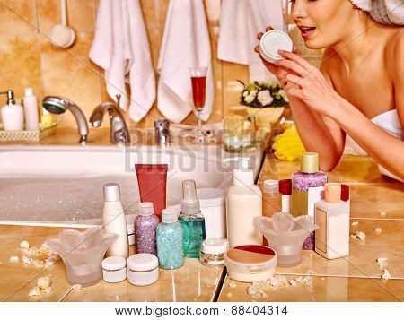 Woman applying moisturizer at bathroom. Cosmetic on foreground.