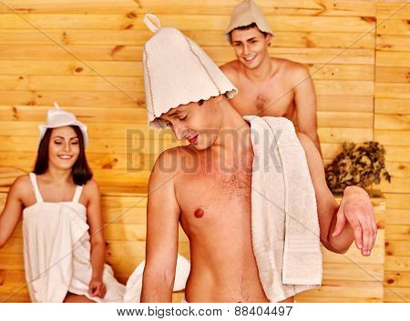 Group people in hat  relaxing at sauna. Three people.