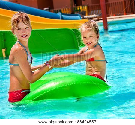 Children sitting on inflatable ring in swimming pool. Kids holding hands