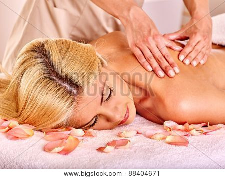 Blond beautiful woman getting massage. Hands on shoulder