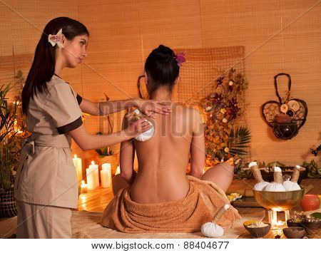Young woman getting thai herbal massage ball. Girl sitting.