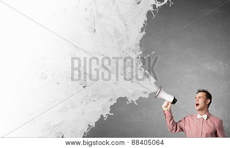 Young funny man screaming emotionally in megaphone