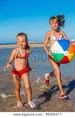 Children holding hands running on  beach. Holding ball.