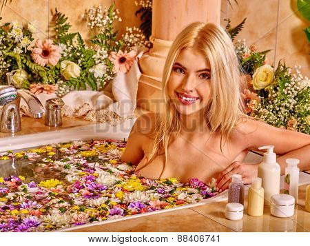 Woman relaxing at water spa. Flower Bath.