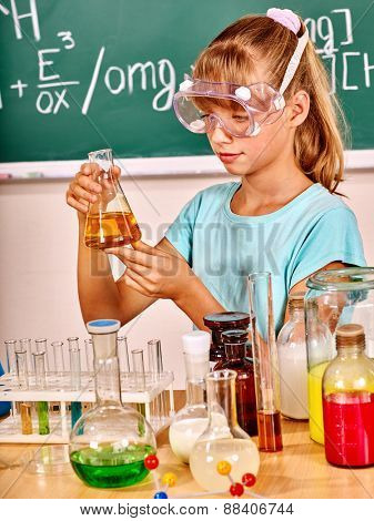 Child holding flask in chemistry class. Mask on face.